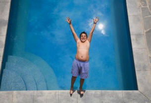picture of latino boy falling into swimming pool