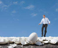 Picture of a business man walking on egg shells