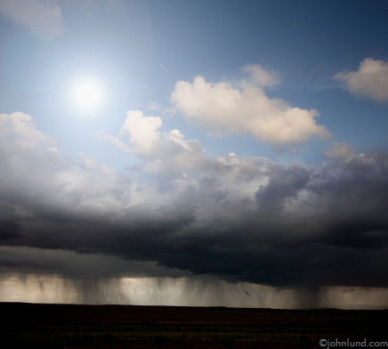 Picture of dark storm clouds with bright sun above the storm