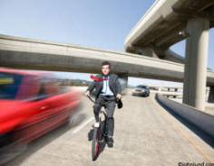 stock picture of man on bicycle on freeway