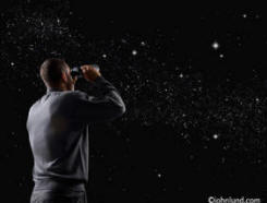Picture of man looking through binoculars at starry night sky