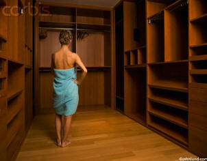 Stock photo of a woman standing in a towel in a empty closet with her back to the camera