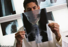 A Hispanic doctor examines an x-ray in this medical stock photo