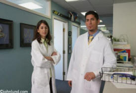 Two doctors, a woman and a man, both ethnic, standing near the nurses station