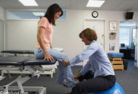 In this medical stock photo a woman physical therapist works on a patients leg in a medical facility