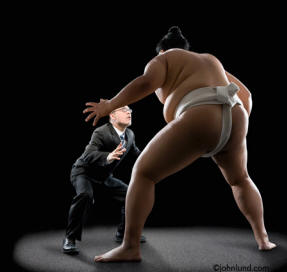 A Japanese Sumo Wrestler squares off with a business man - ethnic stock photo