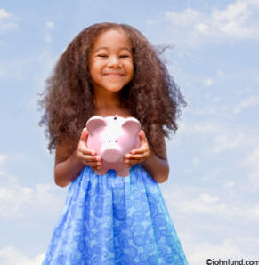 Adorable young black girl with a pink piggy bank - an ethnic stock photo