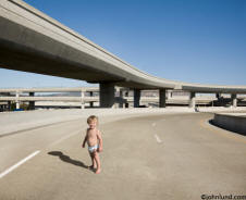 Pictures of a baby in diapers standing alone on a freeway showing Risk and danger