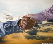 Against a bold sunrise two hands clasp each other in a firm handshake denoting agreement, teamwork and alliance