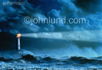 Lighthouse Beacon Pics - In the darkness of stormy night a lighthouse casts beam over the wind whipped waves.
