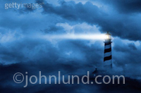 Lighthouse Lights - Concept stock photo of a lighthouse in the fog with beam of light shooting from lighthouse across the cloudy sky.