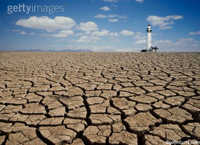 Unusual Lighthouses - Picture of a lighthouse standing in a vast field of dry cracked land or mud  illustrating ecology issues, global warming and conservation