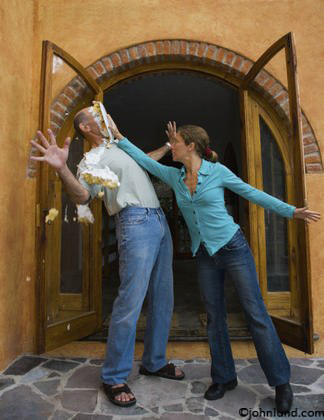 A woman pushes a cake into a man's face in this humorous concept stock picture illustrating relationship issues; a twist on