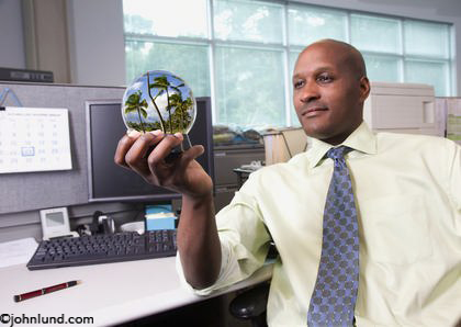 Picture of a businessman in his office gazing at a snowglobe and dreaming about a tropical vacation. An African American executive sits in his offices and gazes into a snowglobe of a tropical beach scene in this stock picture.