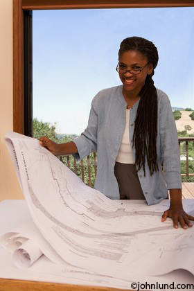 african american woman architect looking at blueprints in her office. Black Bedroom Furniture Sets. Home Design Ideas