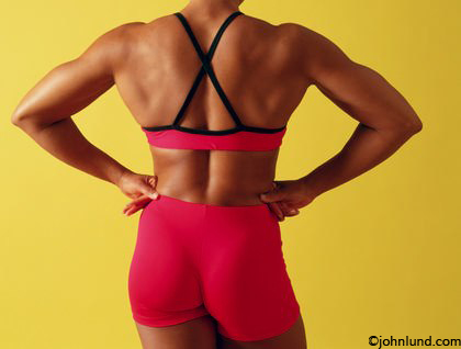 A woman bodybuilder's well muscled back and shoulders are displayed in this image. The woman has on a two piece outfit that is bright red with black trim. Her hands are on her hips and she is facing away from the camera.