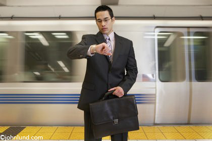 A Chinese American business man checks his watch while holding a briefcase and with a subway train speeding behind him