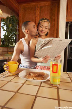 An African American man and his Asian American woman partner share the newspaper and breakfast in their kitchen. They are sitting at the counter and she is sitting on his lap. She has the newspaper in her hands. Glass of orange juice on the counter.