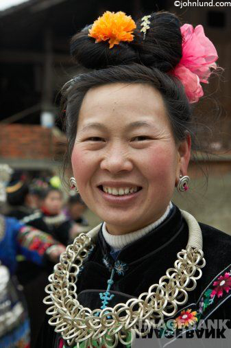 Portrait of a rural tribal woman in China wearing traditional dress and celebrating a festival.