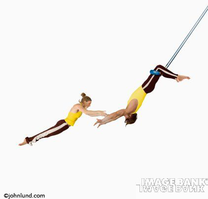 Trapeze artists catching each other in a display of skill, Timing, teamwork and trust.