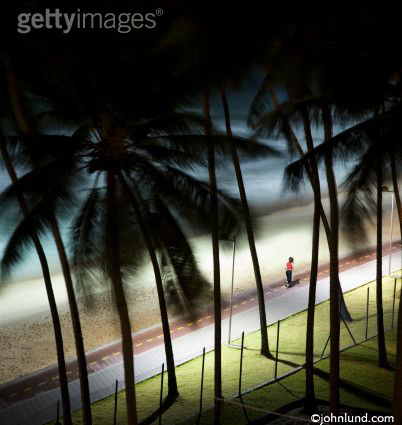 Photo of a woman jogging on a Brazilian beach far below. Shot taken from 8th floor hotel room window. Palm trees abound.