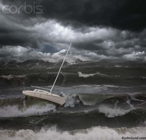 Stock photo pictures of a sail boat in a dark and stormy sea, being tossed about by violent waves and in danger of capsizing and sinking.