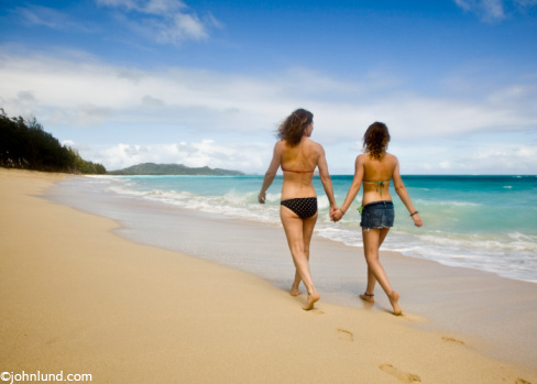 Picture of a mother and daughter hand-in-hand walking on the beach in Hawaii while on vacation. Beautiful scenic beach with gorgeous tropical water and blue sky.