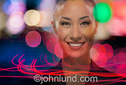 A beautiful Asian business woman smiles as she is surrounded by city lights and streaking colored lines in a stock photo about success and the speed of business.
