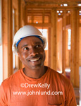 Picture of a happy smiling African American construction worker inside a home under construction. Framing carpenter photo. Black man wearing a white hard had and an oragne t-shirt at a construction site.  Job site pics.