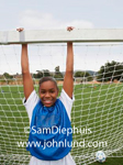 Picture of a young black girl wearing a blue and white jersey and hanging onto the goalie net. The girl is playing soccer and she is the goalie.
