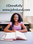 Picture of a happy young African American high school student sitting at her desk reading a textbook.  She is smiling and looking at the camera.  She has long black frizzy hair and is wearing a pink blouse.