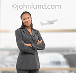 Portrait of an African American woman executive in an airport setting with a commercial jet taking off in the background.