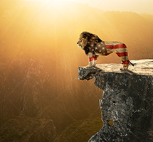 A lion, multiple exposed with the American Flag, stands on a cliff overlooking his domain in an image about American strength and Patriotism.