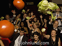 An angry audience throws tomatoes and lettuce at the speaker in this humorous public speaking photo.