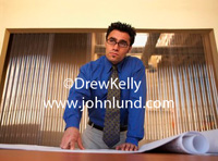 A businessman in his office leaning on a set of blue prints sitting on his conference room table.  He is wearing a deep blue shirt and a neck tie. He has dark hair and is wearing glasses.  Serious look on his face as he looks out past the camera.