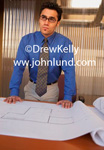 A distinguished looking architect and businessman stands in front of a set of blueprints for a new building with his hands palm down on the prints.  The blueprints are laying on the conference table.