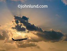 An ascending commercial airliner is silhouetted against