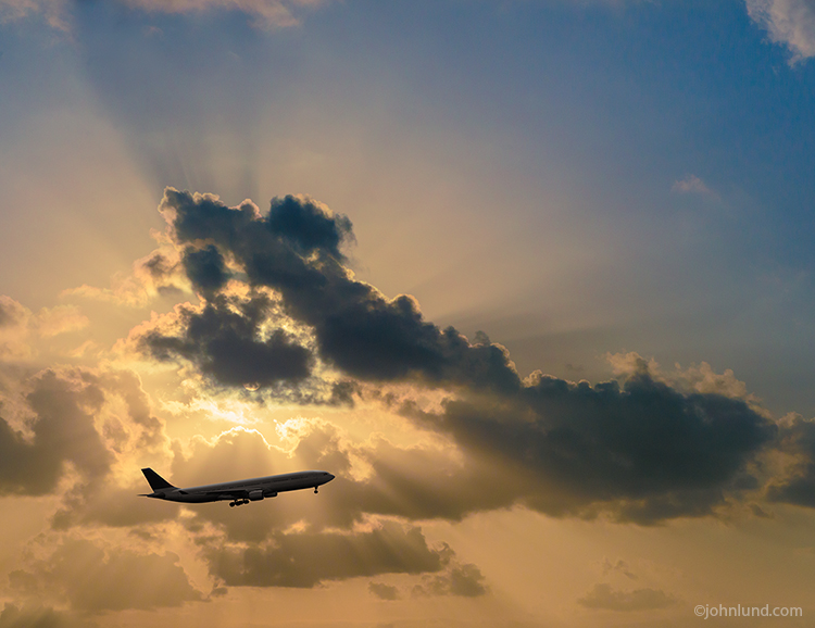 "An ascending commercial airliner is silhouetted against ""God Rays"" streaming out from behind golden clouds in an image about travel, transportation, vacations and getting away from it all."