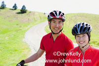 Picture of an Asian couple standing with their bicycles on a country road in green grassy rolling hillside country. Advertising photos of healthy active lifestyles.