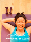 This Asian American woman of Japanese heritage is doing crunches for her morning work out. She is laying on her back, hands under her head, with the camera looking straight down at her face.