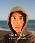 Close up portait of an asian man wearing a hoodie. The Asian man is looking directly at the camera and the out-of-focus ocean is in the background. Middle aged Asian man pic.