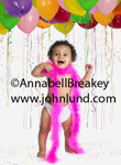 A baby  is wearing a pink feather boa and in a room full of balloons and confetti.  Baby party pic. Cute black baby standing and wearing a cloth diaper and a pink boa under a canopy of multi-colored balloons.