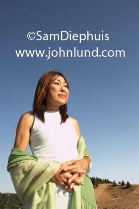 Photo of a middle aged baby boomer Asian woman standing outdoors with a white dress and a green shawl set against a clear blue sky in Northern California.