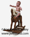 Fun baby picture of an infant riding on a wooden rocking horse. The baby has a suprised look, or maybe terrified look on his face. Funny infant picture.