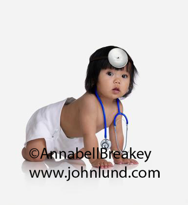 Asian baby wearing a stethascope.  Cute adorable little baby girl with long hair is wearing a stethascope and a cloth diaper and crawling on her hands an knees on a white background