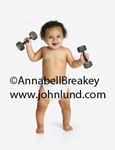 Funny picture of a baby working out with dumbbells. Hilarious photo of a weight lifting baby.  Cute baby wearing a diaper and with a dumbbell in each hand.