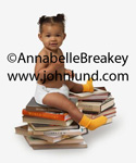 Cute adorable black baby with her hair in pigtails, wearing a diaper, and sitting on a pile of books. She is wearing bright yellow socks.  Black baby pic.