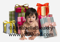 A baby is crawling amid gift wrapped packages with bows and ribbons. Happy little baby in a pile of beautifully wrapped gifts on a white background.  The baby is on all fours and facing the camera.