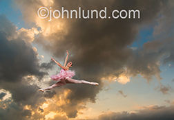 A ballerina in a pink tutu leaps outdoors below gathering storm clouds in a stock photo about skill, dedication, freedom and beauty.
