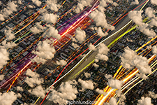 A high-altitude photo showing colored lights streaking across a city below the clouds in a metaphor for cloud computing, bandwidth and Internet connections.